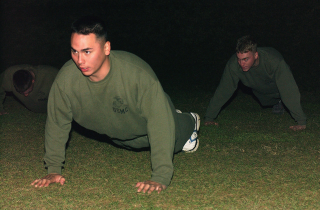 Lance Corporal (LCPL) Anthony Sedillo, a rifleman with the 2nd Battalion, 3rd Marines, waits in the pushup positions at the start of the morning's physical training, to prepare for cold climate deployments