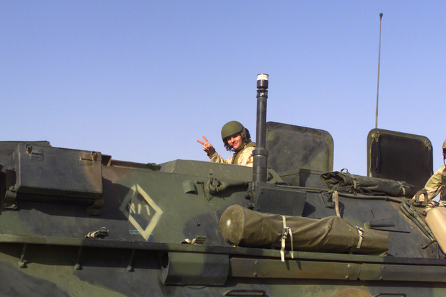 A Marine, 7th Marine Regiment, Camp Pendleton, California, in a FOX M93A1 Nuclear, Biological, and Chemical Reconnaissance System (NBCRS) vehicle flashes a Victory sign as they patrol the camp during Operation ENDURING FREEDOM