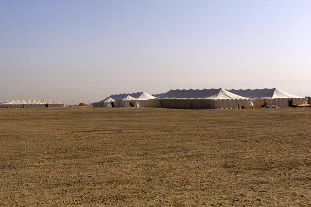 A view of housing area with General Purpose Large tents at Camp Coyote in Kuwait surrounded by a vast landscape of sand