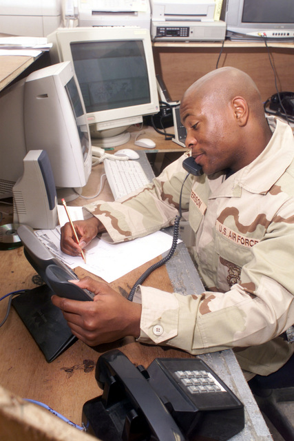 US Air Force (USAF) AIRMAN (AMN) Sean Patterson, the 379th Expeditionary Civil Engineering Squadron (ECES), Fire Department, mans the telephone inside the alarm room, while deployed at Al Udeid Air Base (AB) Qatar