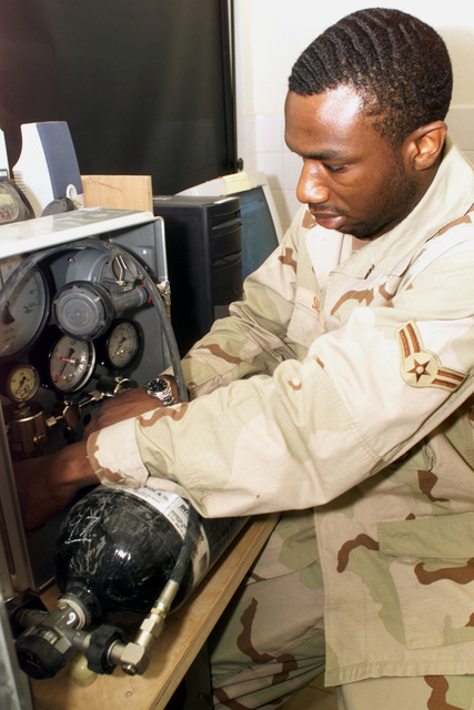 US Air Force (USAF) AIRMAN First Class (A1C) Roy Sanders, 379th Expeditionary Civil Engineering Squadron (ECES), inspects and refills an oxygen canister used by firefighters at Al Udeid Air Base (AB) Qatar