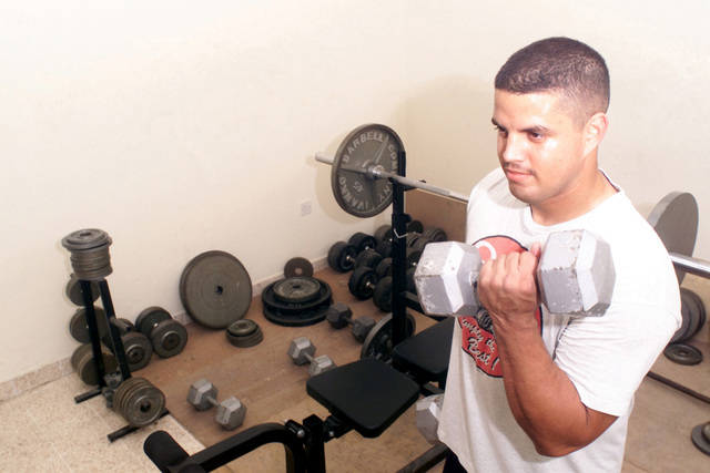 US Air Force (USAF) STAFF Sergeant (SSGT) Joseph Rivera, 379th Expeditionary Civil Engineer Squadron (ECES), works out using free weights inside the Fire Departments exercise room at Al Udeid AB Qatar