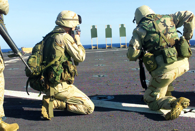 Lance Corporal (LCPL) Lee Dunn, USMC, Motor Transport, 1ST Light Armored Reconnaissance, 1ST Marine Division, Camp Pendleton, California, takes aim as he prepares to fire his 5.56mm M16A2 rifle at a target on the range set up on the rear deck of the USS Pearl Harbor (LSD 52) during Operation ENDURING FREEDOM