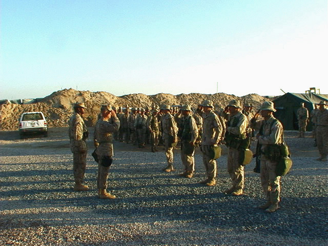 Major General (MGEN) James N. Mattis, USMC, Commanding General, 1ST Marine Division (MAR DIV), returns a salute from Marines of 1ST Battalion (BN) 4th Marines about to be promoted, at Camp Commando, Kuwait while forward deployed in support of Operation ENDURING FREEDOM. To the General left is Sergeant Major (SGM) Juan Duff, Division Sergeant Major