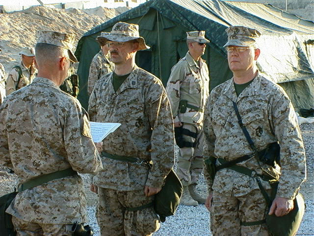 Major General (MGEN) James N. Mattis, USMC, Commanding General, 1ST Marine Division (MAR DIV), reads the Promotion Warrants for Marines of Headquarters Battalion (HQ BN), 1ST Marine Division (MAR DIV), about to be promoted, at Camp Commando, Kuwait while forward deployed in support of Operation ENDURING FREEDOM
