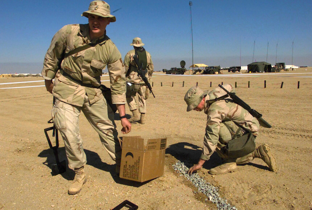 Marines, armed with a 5.56 mm M16A2 rifle, build a topographical model simulating the terrain. This will aid the troops visualize the battlefield as a whole as they plan their maneuvers during Operation ENDURING FREEDOM at Camp Coyote, Kuwait
