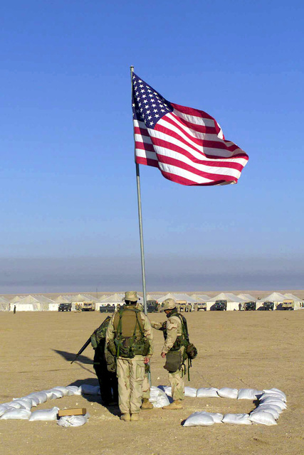 Marines from Headquarters Company, 7th Marine Regiment, Twentynine Palms, California, raise the American flag over the Kuwait Desert at Camp Coyote