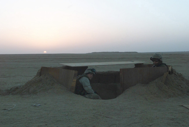Marines from the 1ST Marine Division (MAR DIV), 7th Marines Regiment, Twentynine Palms, California, take their position in their fighting hole as the sun sets during Operation ENDURING FREEDOM at Camp Coyote, Kuwait