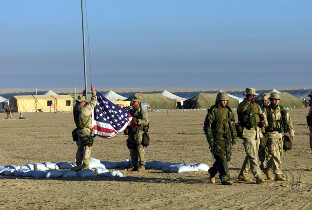 Marines of the 7th Marines Regiment/ 7th Marines, Twentynine Palms, California, raise the colors at Camp Coyote in Kuwait during Operation ENDURING FREEDOM