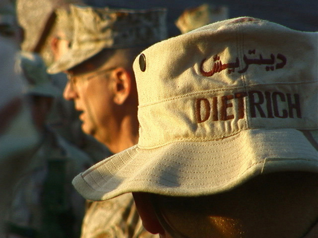 The hat of Corporal (CPL) Gregory C. Dietrich, USMC, Operations Clerk, as he listens to Major General (MGEN) James N. Mattis, USMC, Commanding General, 1ST Marine Division (MAR DIV), address the Marines of Headquarters Battalion (HQ BN) after a promotion ceremony at Camp Commando Kuwait during Operation ENDURING FREEDOM. The hat is embroidered with CPL Dietrichs name in English and Arabic