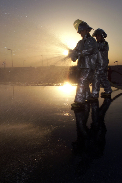 US Air Force (USAF) AIRMAN First Class (A1C) Heath Bichel (foreground) and USAF A1C Michael Long, both assigned to the 379th Expeditionary Civil Engineering Squadron (ECES), run an operations check on a fire hydrant hose at Al Udeid Air Base (AB) Qatar. The setting sun silhouettes the image