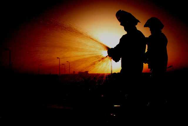 US Air Force (USAF) AIRMAN First Class (A1C) Heath Bichel (left) and USAF A1C Michael Long, both assigned to the 379th Expeditionary Civil Engineering Squadron (ECES), run an operations check on a fire hydrant hose at Al Udeid Air Base (AB) Qatar. The setting sun silhouettes the image