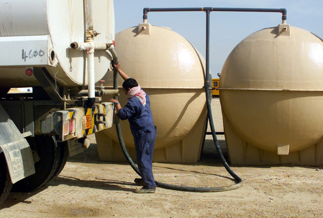 A Kuwaiti worker refills the water tanks of a showering facility for the 7th Marine Regiment at Camp Coyote, Kuwait, during Operation ENDURING FREEDOM