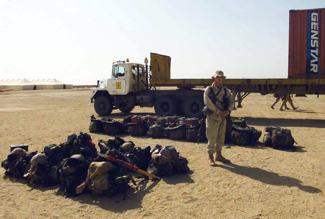 A Marine from the 1ST Battalion 7th Marines Regiment, Bravo Company, stands by the gear of recent arrivals at Camp Coyote, Kuwait, during Operation ENDURING FREEDOM