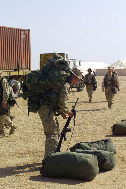 A Marine with 1ST Battalion 7th Marines Regiment, Twentynine Palms, California, unloads his gear as he arrives at Camp Coyote, Kuwait, during Operation ENDURING FREEDOM