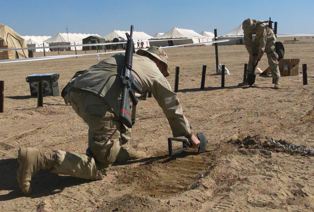 A pair of 7th Marine Regiment/7th Marines, Fire Support Command Center (FSCC), begin the process of building a topographical model simulating the terrain of an area in Kuwait. The model will aid the troops to visualize the battlefield as a whole as they plan their maneuvers during Operation ENDURING FREEDOM at Camp Coyote, Kuwait.  (Duplicate image, see also DMSD0507369 or search 030202M5753Q041)