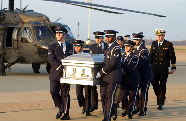 A US Air Force (USAF) Honor Guard transports a coffin carrying the remains of a crewmember from the space shuttle Columbia mishap, across the flight line at Barksdale Air Force Base, Louisiana (LA). Following the honor guard is Commander (CDR) Harold Robinson, US Navy Reserve (USNR) Chaplain. A USAF HH-60 Black Hawk helicopter is parked in the background