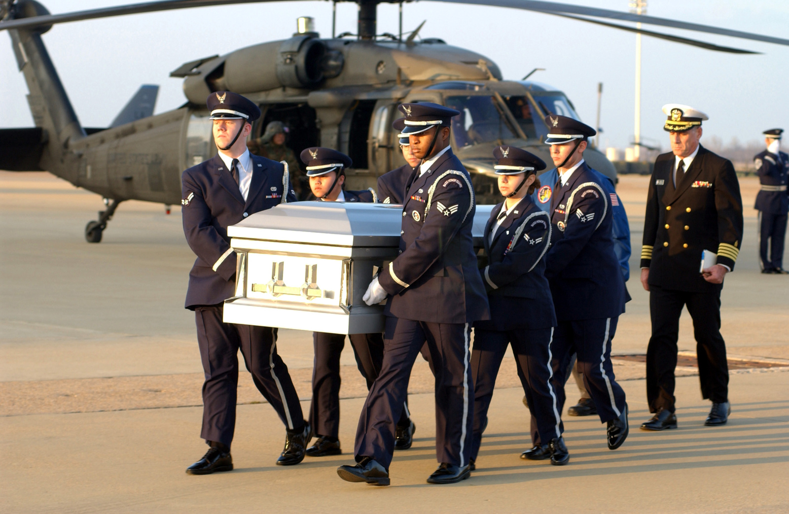 A US Air Force (USAF) Honor Guard transports a coffin carrying the remains of a crewmember from the space shuttle Columbia mishap, across the flight line at Barksdale Air Force Base, Louisiana (LA). Following the honor guard is Commander (CDR) Harold Robinson, USN Navy Reserve (USNR) Chaplain. A USAF HH-60 Black Hawk helicopter is parked in the background