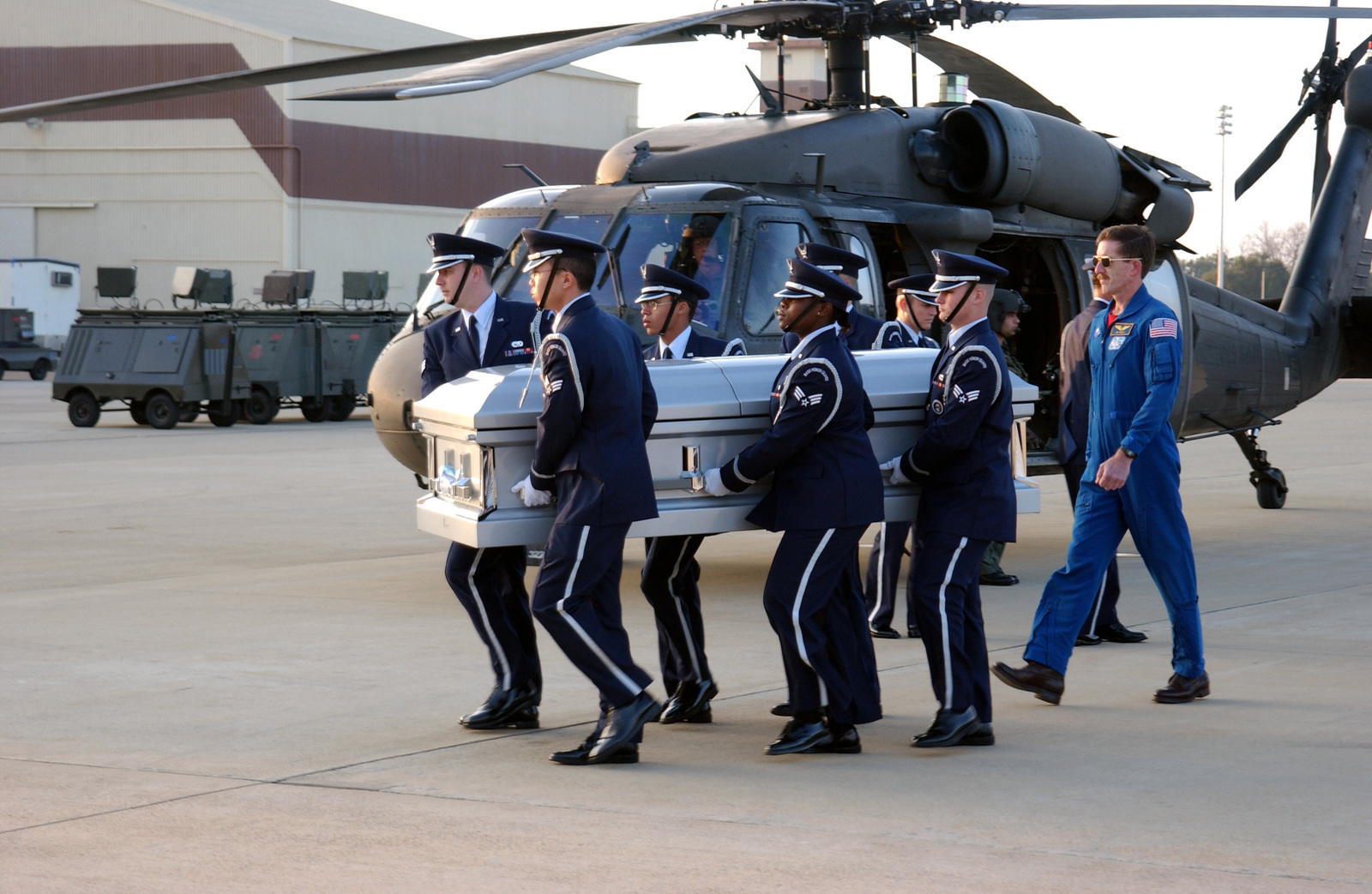 A US Air Force (USAF) Honor Guard transports a coffin carrying the remainsof a Space Shuttle Columbia crewmember, across the flight line at Barksdale Air Force Base, Louisiana (LA). Accompanying the Honor Guard is National Aeronautics Space Administration (NASA) Astronaut Jim Reilly. USAF HH-60 Black Hawk helicopter is parked in the background