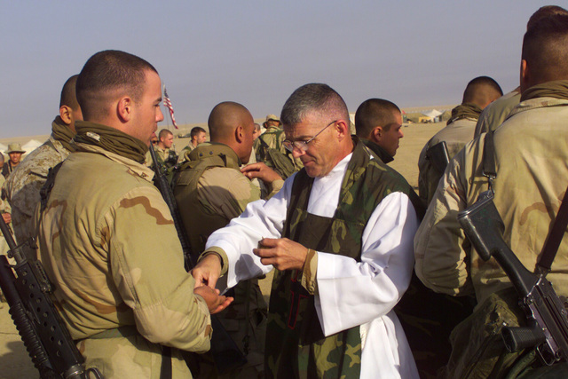 At Mass, the Catholic Chaplain places a wafer representing the Eucharist into the hands of a Marine during the communion ceremony at Camp Coyote, Kuwait during Operation ENDURING FREEDOM