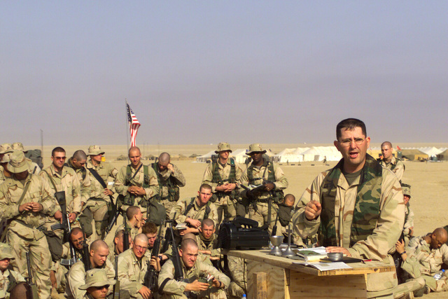 Chaplain Lieutenant (LT) Darren Stennett, USN, assigned to the 3rd Battalion 7th Marines, Twentynine Palm, California, gives a message from the book of Joshua to his Marine congregation during the Protestant Service held at Camp Coyote, Kuwait, during Operation ENDURING FREEDOM
