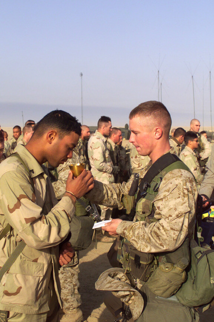 Corporal (CPL) Breton Jeffery, (left), USMC, India Company 3rd Battalion 4th Marines takes a sip from a chalice during the communion ceremony at the Catholic Mass held at Camp Coyote, Kuwait during Operation ENDURING FREEDOM