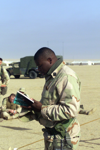 Hospital Corpsman Toren Compton, USN, assigned to Headquarters Company 3rd Battalion 7th Marines, Twentynine Palm, California, reads aloud a passage from the Old Testament during the Protestant Service held at Camp Coyote, Kuwait, during Operation ENDURING FREEDOM