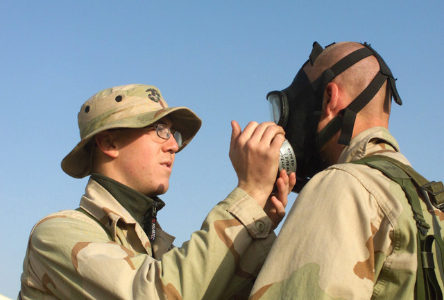 Lance Corporal (LCPL) Julian Cofer, USMC, (left), 7th Marines Head Quarters Company Nuclear Biological Chemical (NBC) checks for air leaks in Private First Class (PFC) Mathew Wrays, USMC, 1ST Combat Engineer, Charlie Company, M40A1 Chemical-Biological mask during a gas mask serviceability inspection at Camp Coyote, Kuwait, during Operation ENDURING FREEDOM