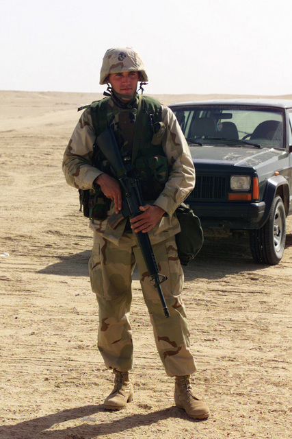 Lance Corporal (LCPL) Nathan Heusdens, USMC, 7th Marine Regiment, armed with a 5.56mm M16A2 rifle, watch over his fellow Marines at Camp Coyote, Kuwait, during Operation ENDURING FREEDOM