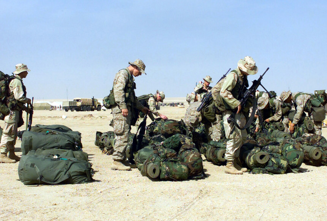 Marines from the 1ST Battalion 7th Marines Regiment, Bravo Company pick up their gear after arriving at Camp Coyote, Kuwait, during Operation ENDURING FREEDOM