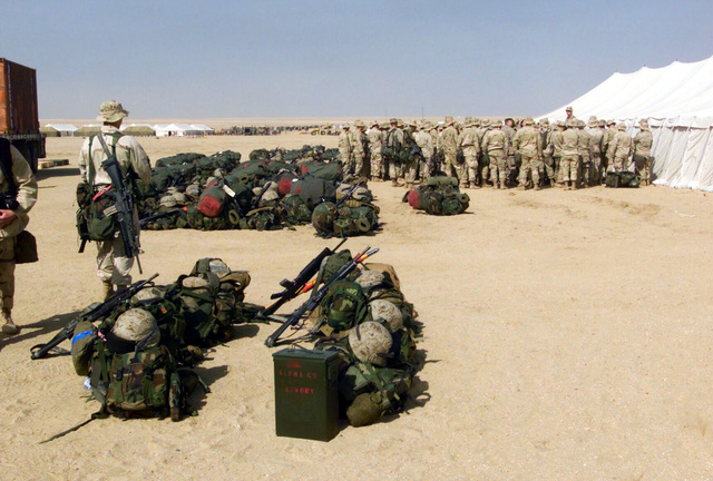 Marines from the 1ST Battalion 7th Marines Regiment, Bravo Company, Twentynine Palms, California, gather for a briefing after just arriving at Camp Coyote, Kuwait during Operation ENDURING FREEDOM. In the foreground, a pair of Marines watch the new arrivals gear