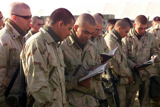 Marines share a hymnbook while singing at the Sunday morning Catholic Mass at Camp Coyote, Kuwait, during Operation ENDURING FREEDOM
