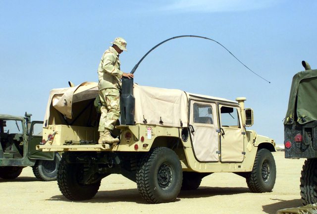 Private First Class (PFC) Luis Uresti, USMC, 7th Marines Regiment, Headquarters Battalion Communications Company, attaches an HF whip (flexible) antenna to the back of an M1035 High-Mobility Multipurpose Wheeled Vehicle (HMMWV) at Camp Coyote, Kuwait, during Operation ENDURING FREEDOM
