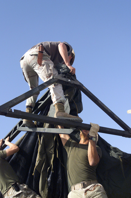 Sergeant (SGT) Hassine Serrano hands the tent skin up to SGT Nicholas Hizer while building the Marine Wing Support Squadron (MWSS) tent at Al Jaber Air Base, Kuwait, in support of Operation ENDURING FREEDOM