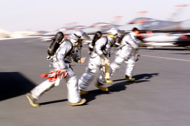 US Air Force (USAF) Firefighters assigned to the 379th Expeditionary Civil Engineers Squadron (ECES), rush across the flight line, during a simulated rescue exercise at Al Udeid Air Base (AB), Qatar. Pictured left-to-right are STAFF Sergeant (SSGT) SSgt Christopher Winters, AIRMAN First Class (A1C) AAron Hiscox, and A1C Jeffery KinKade