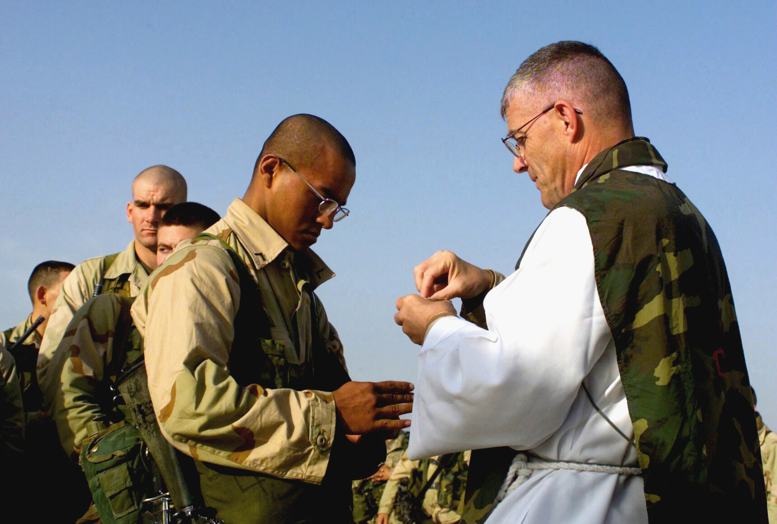 """US Marine Corps (USMC) Private First Class (PFC) Ricardo Castillo, 7th Marines3rd Battalion, 4th Marines (3/4) Weapons Company attends the morning Catholic services held by US Navy (USN) Lieutenant (LT) William """"Bill"""" Devine, Chaplain, early morning Sunday at Camp Coyote, Kuwait"""