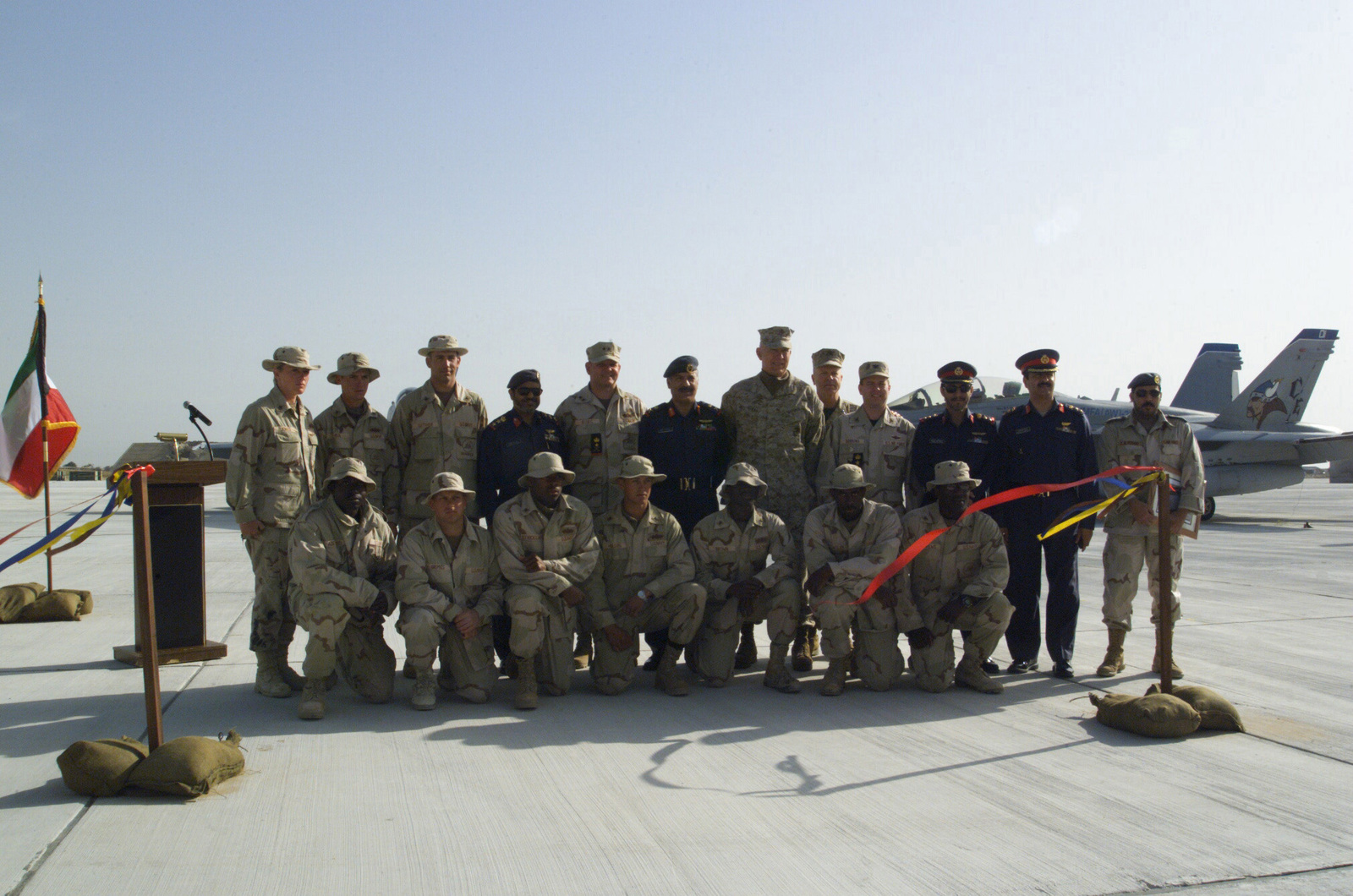 US Navy Sea Bees pose for a group photograph with US Military and State of Kuwait Officials following a ribbon cutting ceremony marking the opening of the new aircraft parking ramp at Ahmed Al Jaber Air Base, Kuwait, during Operation ENDURING FREEDOM. Included in the photo are US Navy (USN) Rear Admiral (RADM) Charles R. Kubic, Commander, First Naval Construction Division, and Commander, Naval Construction Forces Command (back row, fifth from the left) and State of Kuwait Major General (MGEN) Yousaf, pictured to RADM Kubics right