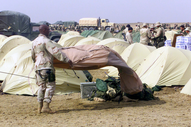 A US Marine with the 2nd Battalion, 5th Marine Regiment, 1ST Marine Division from Camp Pendleton, California, struggles against the wind while he sets up his personal desert tent at Camp Coyote in northern Kuwait, during Operation ENDURING FREEDOM