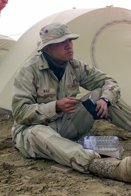 Lance Corporal (LCPL) Richard P. Wade, from Rockville, Maryland, assigned to the 2nd Battalion, 5th Marine Regiment, 1ST Marine Division from Camp Pendleton, California, enjoys a meal at Camp Coyote in northern Kuwait, during Operation ENDURING FREEDOM