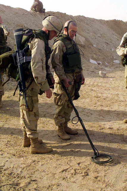Sergeant (SGT) Jason Wittling (left), USMC, with his 5.6 mm M16A2 rifle slung over his shoulder, observes as Private First Class (PFC) James Parsons, USMC, practices the operation of the ANPSS 12 Mine Detector at Camp Coyote, Kuwait