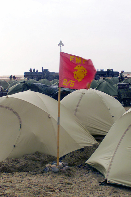 The 2nd Battalion, 5th Marine Regiment, 1ST Marine Division from Camp Pendleton, California, unit guide-on flaps in the wind next to personal desert tents at Camp Coyote in northern Kuwait, during Operation ENDURING FREEDOM