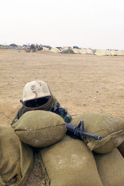 US Marine Private First Class (PFC) Ralph A. Sarabia, from Hacienda Heights, California, assigned to the 2nd Battalion, 5th Marine Regiment, 1ST Marine Division, Camp Pendleton, California, stand watch behind a sandbag wall with his Colt 5.56 mm M16A2 Rifle ready at Camp Coyote in northern Kuwait