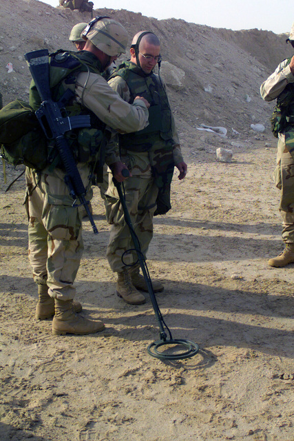 US Marine Sergeant (SGT) Jason Wittling, from Ashland, Wisconsin observes as Private First Class (PFC) James Parsons, of Wesson, Mississippi practices the operation of the ANPSS 12 Mine Detector at Camp Coyote, Kuwait during Operation ENDURING FREEDOM