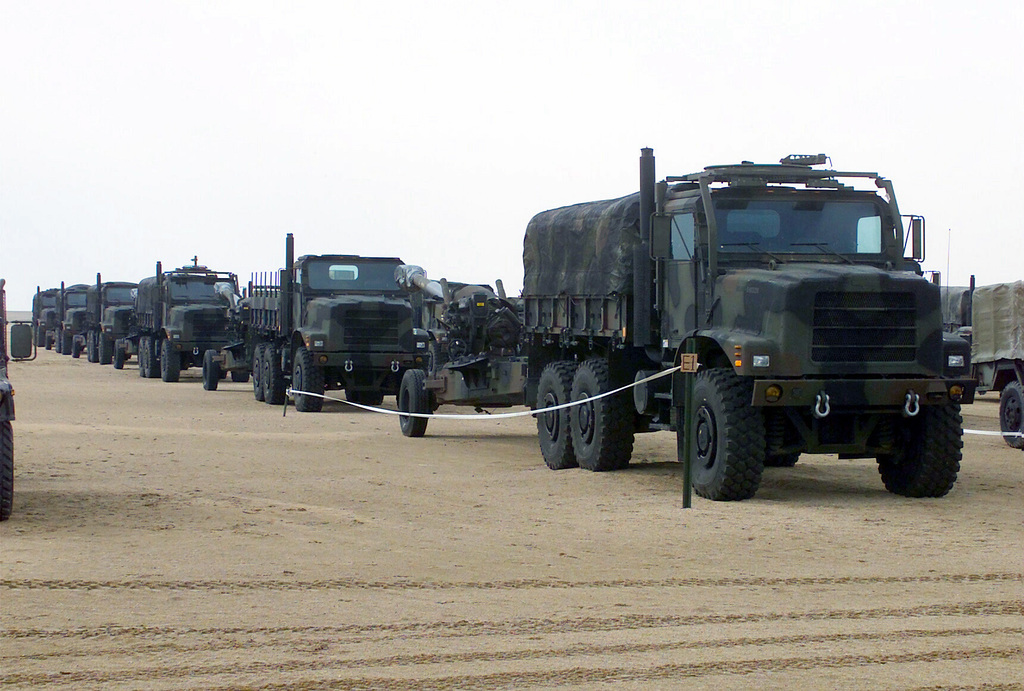 A marshalling yard is filled with MK-23 trucks and M198 155mm Towed Medium Howitzer artillery pieces, in support of Operation ENDURING FREEDOM