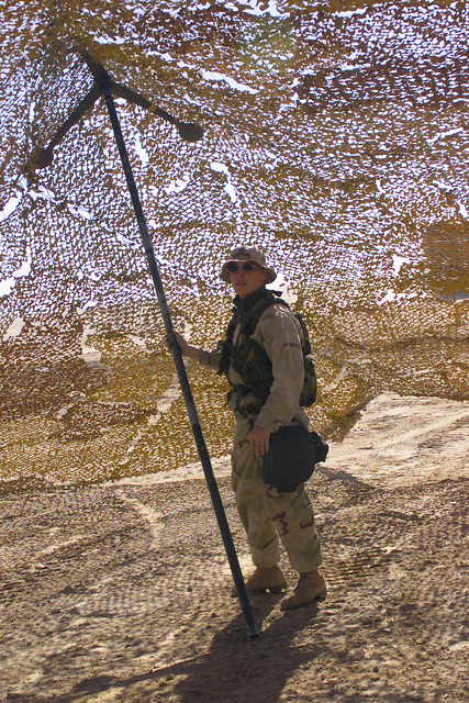 A US Marine Corps (USMC) Marine assigned to Headquarters, 5th Marine Regiment, 1ST Marine Division, sets up a camouflaged net at Camp Coyote in Northern Kuwait during Operation ENDURING FREEDOM