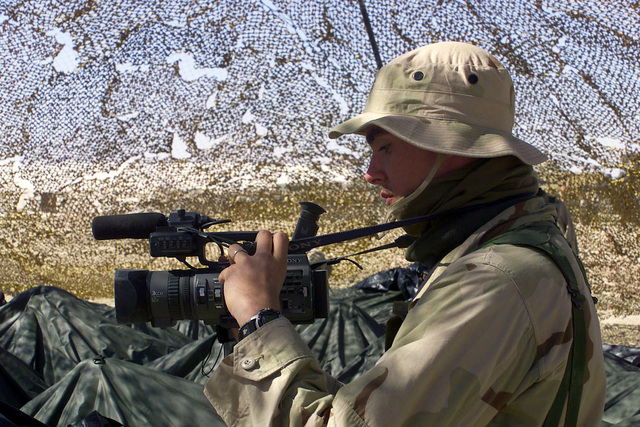 A US Marine Corps (USMC) Videographer assigned to Headquarters, 5th Marine Regiment, 1ST Marine Division, documents activities at Camp Coyote in Northern Kuwait during Operation ENDURING FREEDOM
