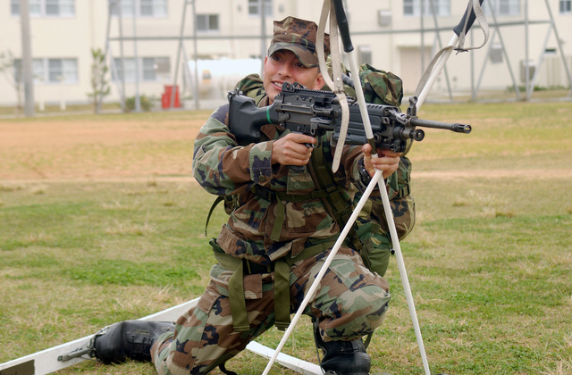 Armed with an FNMI 5.56mm M249 Squad Automatic Weapon (SAW), US Marine Corps (USMC) Corporal (CPL) Chris Garza, a rifleman from 2nd Battalion, 3rd Marines, goes into a kneeling position during a class on firing stances while wearing skis