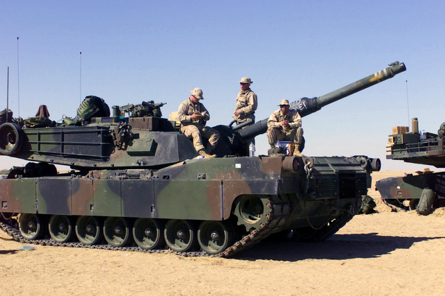 The US Marine Corps (USMC) personnel from the 2nd Tank Battalion, 2nd Marine Division based at Camp Lejeune, North Carolina, take a break on their M1A2 Abrams Main Battle Tanks (MBT) during their training at Camp Coyote in northern Kuwait (KWT), in support of Operation ENDURING FREEDOM