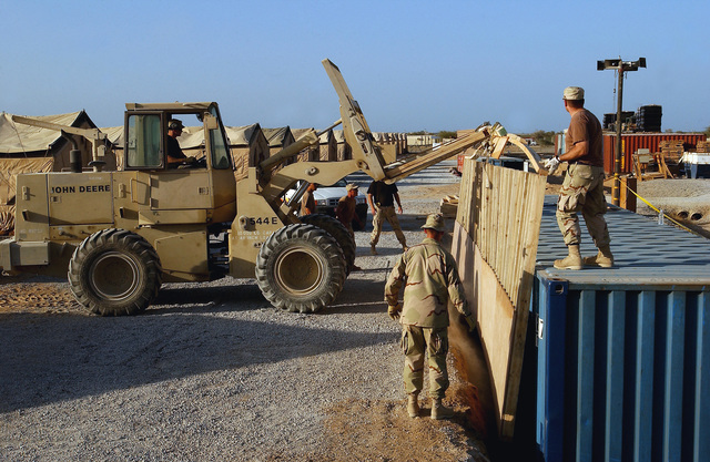 US Air Force (USAF) members, deployed to the 320th Expeditionary Civil Engineering Squadron, use a John Deere 10k forklift to guide a support wall into the excavation along the side of a protective bunker at a forward-deployed location. The bunkers are part of the continuous build up at forward-deployed locations supporting Operation ENDURING FREEDOM