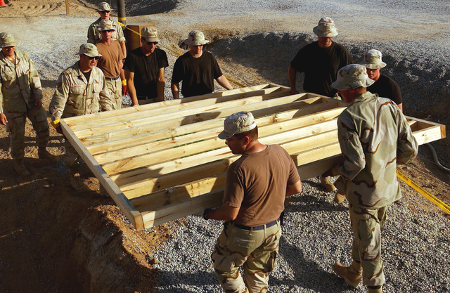 US Air Force (USAF) members, deployed to the 320th Expeditionary Civil Engineering Squadron (ECES), lug a ten-foot section of a support wall for a protective bunker at a forward-deployed location. The bunkers are part of the continuous build up at forward-deployed locations supporting Operation ENDURING FREEDOM
